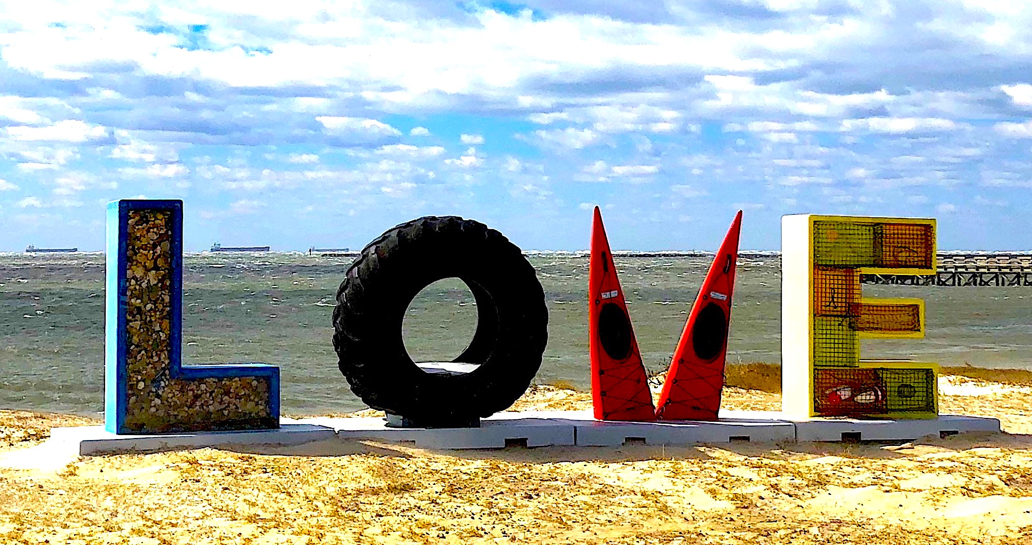 L O V E letters, O in shape of tire, V in shape of Kayaks with background of chesapeake bay